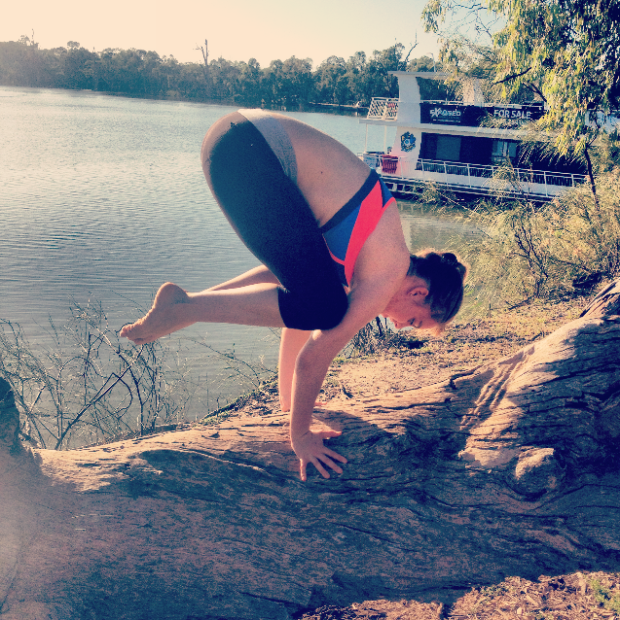 "Bakasana ""crow"" pose on a log."